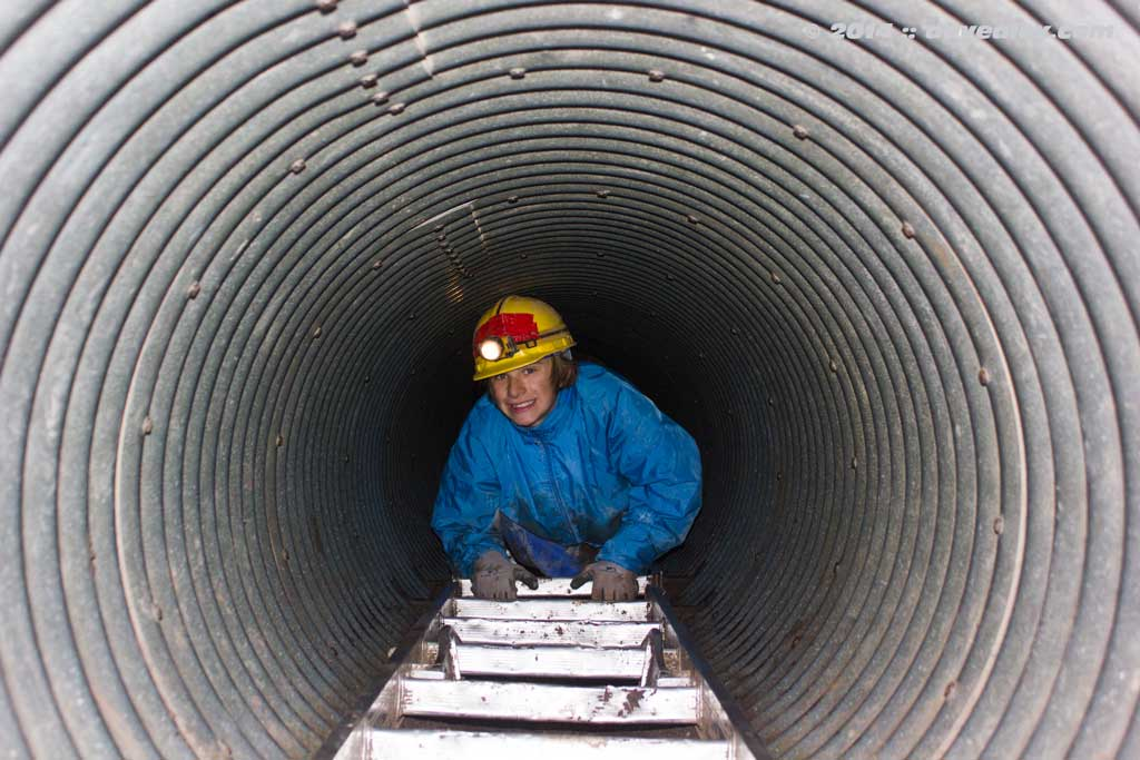 Hunter coming out of the culvert entrance.  The ladder in the culvert has many rungs missing and many  more broken.